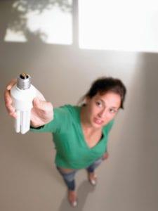 Woman reaching up to a high lightbulb